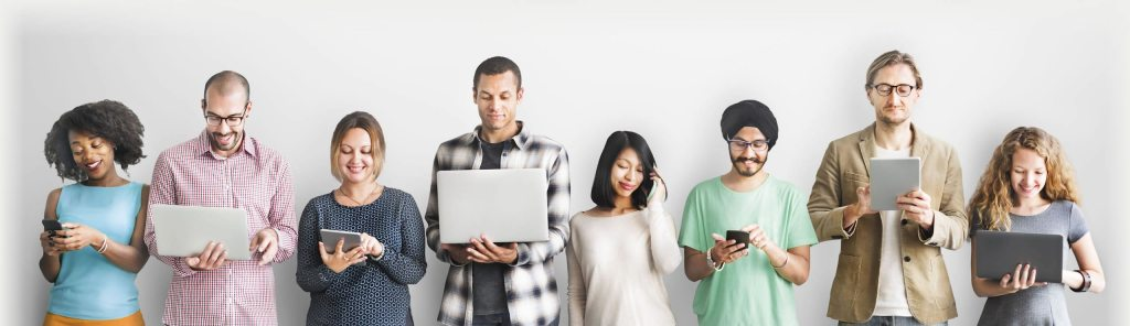 Image of a diverse group of people in a row, smiling and looking at their own electronic devices